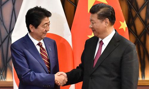 Abe (trái) bắt tay ông Tập bên lề hội nghị APEC ở Việt Nam tháng 11/2017. Ảnh: AP.