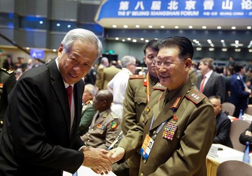 Bộ trưởng Quốc phòng Singapore Ng Eng Hen (trái) bắt tay Thứ trưởng Quốc phòng Triều Tiên Kim Hyong-ryong tại Diễn đàn An ninh Hương Sơn ở Bắc Kinh hôm nay. Ảnh: Reuters.