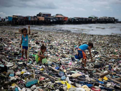 Trẻ em thu gom chai nhựa trên một bãi biển ở vịnh Manila, Philippines hồi tháng 8. Ảnh: AFP.