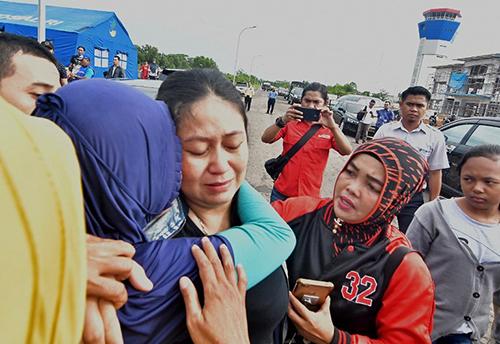 Một phụ nữ đau đớn vì mất chồng con trên chuyến bay JT610. Ảnh: AFP