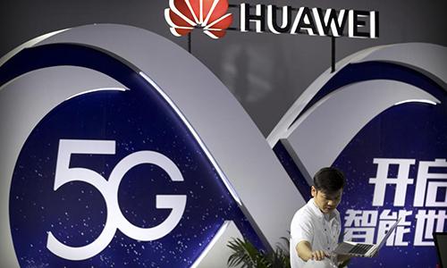 Nhân viên Huawei dùng laptop giới thiệu công nghệ 5G tại Triển lãm PT tại Bắc Kinh, Trung Quốc tháng 9/2018. Ảnh: AP.