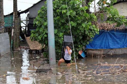 Người dân Philippines sơ tán đồ đạc khỏi ngôi nhà ngập lụt ở tỉnh Aurura trên đảo Luzonhôm 29/10. Ảnh: AFP.
