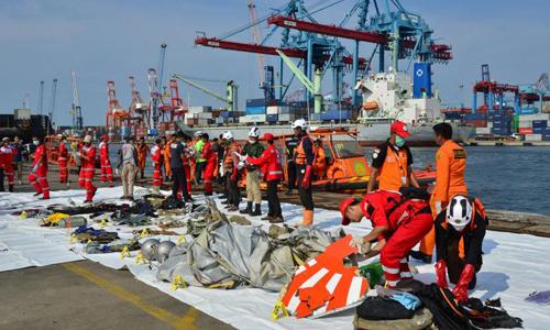Các nhân viên cứu hộ sắp xếp những mảnh vỡ của chiếc máy bay Boeing 737 và đồ vật của các nạn nhân tại cảng Tanjung Priok, Jakarta, Indonesia. Ảnh: Reuters.