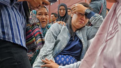 Putri Pratiwi khóc thương chồng và con traibên ngoài bệnh viện cảnh sát ở Jakarta dưới cái nóng của Jakarta,