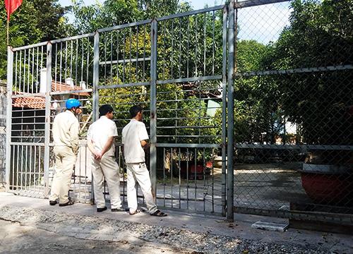 Lực lượng quy tắc đành đứng ngoài khi không có lệnh mở cửa của chủ khu biệt thự bị cưỡng chế. Ảnh: Nguyễn Đông.