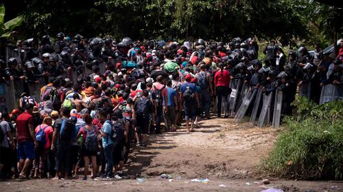 Đoàn di cư từ Trung Mỹ đụng độ với cảnh sát Mexico tại biên giới. Ảnh: AP.