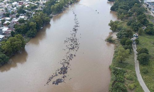 Đoàn di cư thứ hai lội qua sông Suchiate ở biên giới Guatemala vàMexico hôm 29/10. Ảnh: AP.