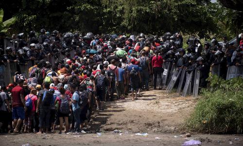 Người di cư Honduras vượt sông để vào lãnh thổ Mexico hôm 21/10. Ảnh: AFP.