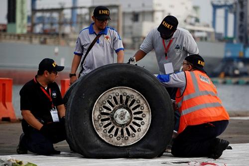 Quan chức Cục Điều tra Hàng không và Ủy ban An toàn Giao thông quốc gia Indonesia kiểm tra phần bánh máy bay tại cảngTanjung Priok,Jakarta hôm nay. Ảnh: Reuters.