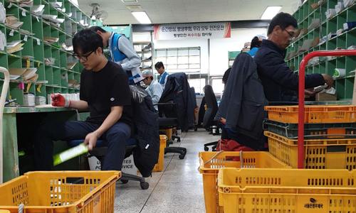 Nhân viên của Cơ quan Bưu chính Hàn Quốc phân loại bưu kiện và thư từ.Ảnh: CNN.