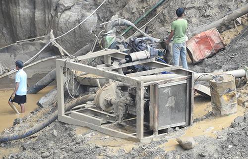 Lực lượng cứu hộ dùng máy bơm cỡ cỡ lớn hút nước trong lòng hang ra ngoài.