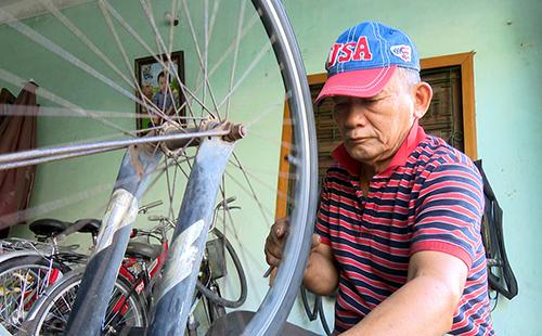 Ông lão sửa xe kiếm tiền lo gia đình cùng chi phí đi học. Ảnh: Thiên Lý