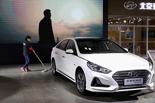 Một công nhân lau sàn cạnh chiếc Sonata Hybrid tại gian hàng của Hyundai Bắc Kinh ở triển lãm tiết kiệm năng lượng hôm 18/10, Bắc Kinh. Ảnh: Reuters/Thomas Peter