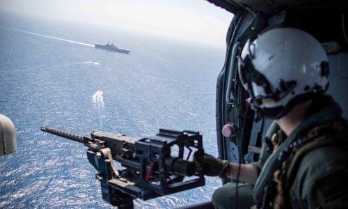 Xạ thủ trực thăng MH-60 theo dõi diễn tập SWATT trên tàu đổ bộ USS Kearsarge. Ảnh: US Navy.