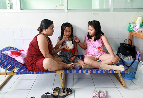 Chị Hạnh chăm con gái 9 tuổi bị sốt xuất huyết ở bệnh viện. Ảnh: Xuân Ngọc