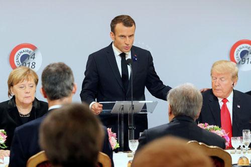 Trong khi Tổng thống Mỹ Donald Trump ngồi cạnh Tổng thống Pháp Emmanuel Macron. Ảnh: Reuters.