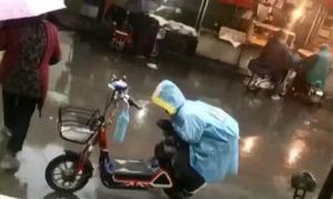 Bé trai Trung Quốc khom người che yên xe cho mẹ dưới trời mưa