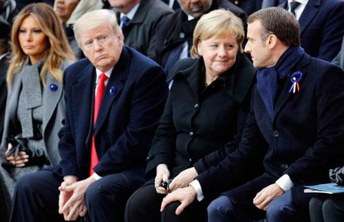 Trump (thứ ba từ phải sang) ngồi dự lễ kỷ niệm trong khi Thủ tướng Đức Merkel và Tổng thống Pháp Macron (phải) trao đổi cùng nhau. Ảnh: Reuters.