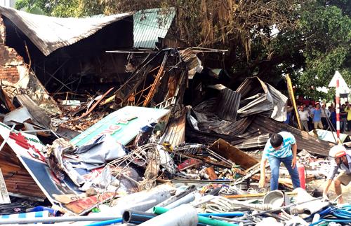 Người của các cửa hàng tìm tài sản trong hiện trường tan hoang sau vụ cháy. Ảnh: Nguyệt Triều.