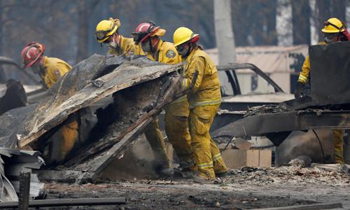Lực lượng tìm kiếm người sống sót trong vụ cháy rừng Camp ở California hôm 13/11. Ảnh: AP.