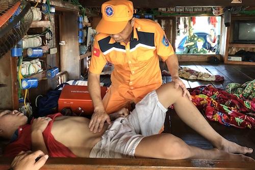 Cán bộ tàu SAR 411 thăm khám cho ngư dân trên tàu cá NA 95889. Ảnh: Trung tâm tìm kiếm.
