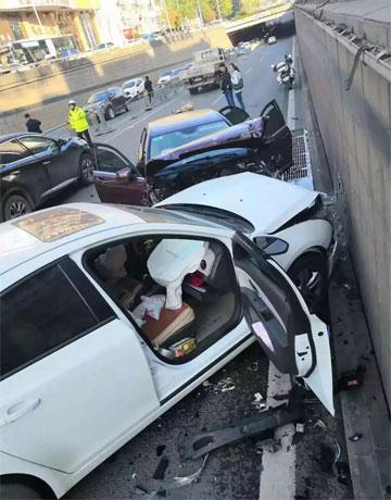 Ngoài chiếc Mercedes nát đầu vì đâm vào tường chắn, một xe sedan màu trắng cũng hỏng nặng phần đầu, túi khí bung.