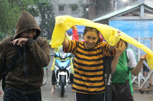Học sinh TP HCM sau giờ tan học trong một cơn mưa lớn. Ảnh: Phạm Phúc.