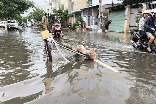 Người dân tháo nắp cống để thoát nước khi Nha Trang ngập sâu. Ảnh: An Phước