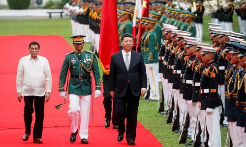 Tổng thống Philippines Rodrigo Duterte (trái) và Chủ tịch Trung Quốc Tập Cận Bình (thứ ba từ trái) duyệt đội danh dự trước cuộc gặp tại Điện Malacanang, Manila hôm nay. Ảnh: Reuters.