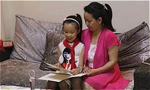 Cai Chengcheng dạy mẹ đọc. Ảnh: SCMP