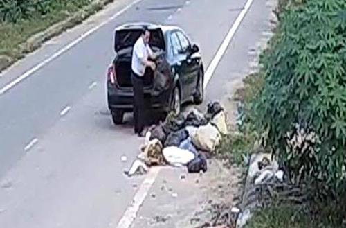 Hình ảnh ông Trí đổ rác tràn ra đường bị camera nhà dân ghi lại.