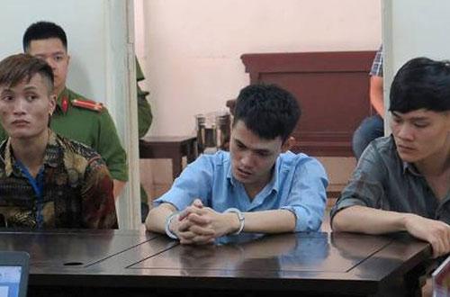 Quân (ở giữa) giả vờ ngờ nghệch khi ra tòa.