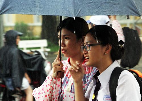 Học sinh THPT Nguyễn Thị Minh Khai (TP HCM)tan học trong cơn mưa. Ảnh: Mạnh Tùng.