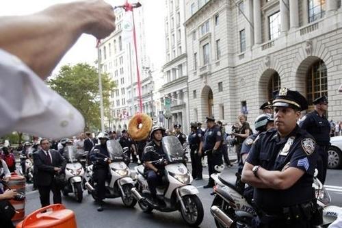 Người biểu tình nhử bánh donut trước mặt cảnh sát. Ảnh: UPI.