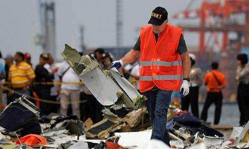 Một nhân viên Ủy ban An toàn Giao thông Quốc gia Indonesia kiểm tra mảnh vỡ của chiếc Boeing 737 MAX 8. Ảnh: Reuters.