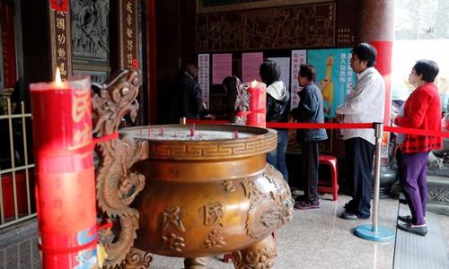 Người dân Đài Loan xếp hàng đi bỏ phiếu tại một địa điểm ở thành phố Cao Hùng ngày 24/11. Ảnh: Reuters.