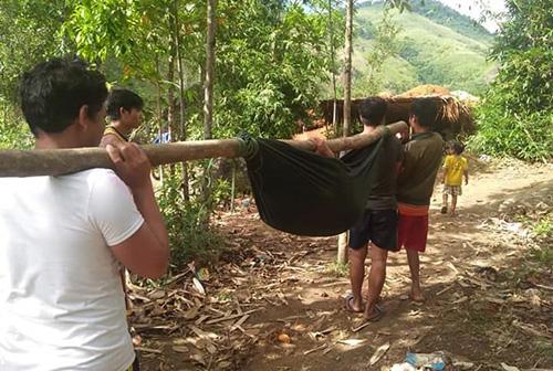 Thanh niên trong làng thay nhau gánh một sản phụ đi sinh. Ảnh: Đắc Thành.