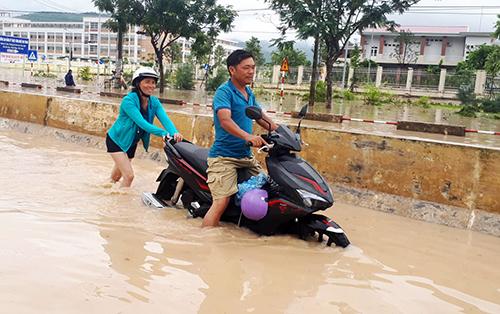 Người dân dắt xe qua khỏi điểm ngập nước trên đại lộ Nguyễn Tất Thành, Nha Trang. Ảnh: Xuân Ngọc