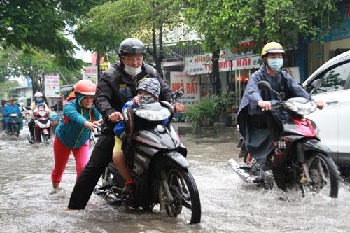 Một gia đình TP HCM đưa con đi học trong cơn mưa ở TP HCM. Ảnh minh họa: Mạnh Tùng.