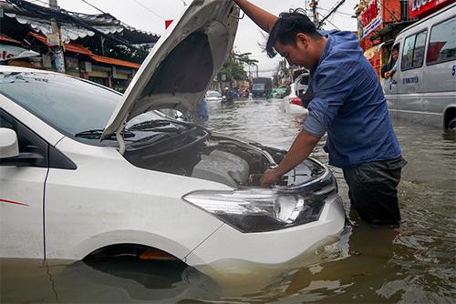 Chiếc xe nằm chịu trận giữa đường khi nước ngập quá bánh xe vào sáng ngày 26/11 tại TP HCM. Ảnh: Quỳnh Trần.