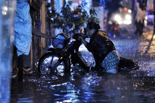 Người dân bì bõm trong nước ngập. Ảnh: Khoa Quỳnh.
