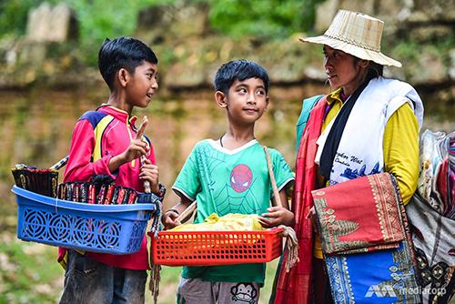 Salik (trái) và em trai Thuch Tithya cùng mẹ bán đồ lưu niệm kiếm sốngở đền Ta Prohm tại Angkor, tỉnh Siem Reap, Campuchia. Ảnh: Mediacorp