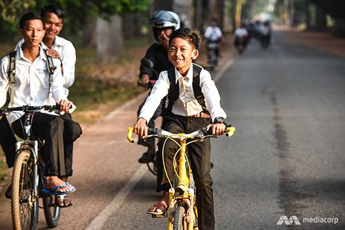 Salik tự đạp xe 3 km mỗi ngày đi học vào buổi sáng và buổi chiều đi bán hàng với mẹ. Ảnh: Mediacorp