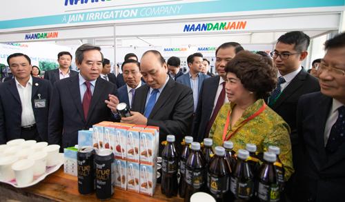 Thủ tướng Chính phủ Nguyễn Xuân Phúc tham quan gian hàng trưng bày sản phẩm của tập đoàn TH và rất quan tâm tới các dòng sản phẩm mới có nguyên liệu tự nhiên.