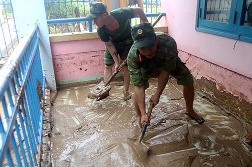 Bộ đội dọn dẹp bùn non trong trường học ở TP Cam Ranh, hôm 26/11. Ảnh: An Phước