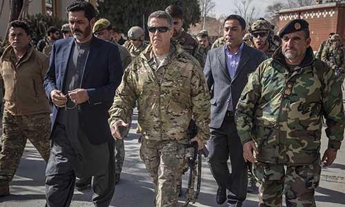 Đại tướng Austin S. Miller (mặc quân phục, đeo kính đen) cầm súng carbine M4 cùng thống đốc tỉnh Wahidullah Kalimzai (thứ hai từ trái sang) đi bộ trên đường phố Ghazni. Ảnh: NATO.