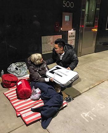Vo Hoai Trung tặng một người vô gia cư ở trung tâm Houston túi ngủ và gối hôm 26/11. Ảnh: Chron