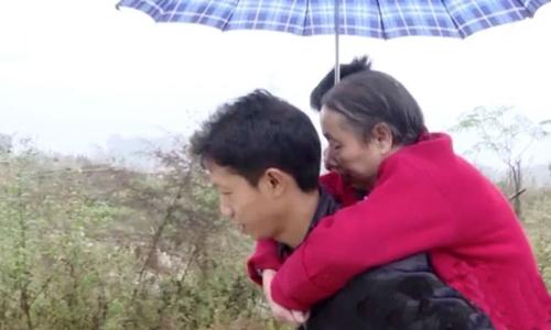 Wang Xianqiang cõng mẹ đi dạo. Ảnh: Weibo.