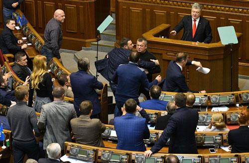Các nghị sĩ đối lập Ukraine hôm 26/11 lao lên đòi Tổng thống Poroshenko đang đứng trên bục phát biểu phải công bố rõ các điều khoản của lệnh thiết quân luật nhưng không được đáp ứng. Ảnh: AFP.