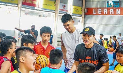 Horace Nguyễn (phải, áo đen) và  Chris Dierker,chàng cầu thủ gốc Việt cao hơn 2m, trong một buổi tập với các em nhỏ tại trung tâm phát triển bóng rổ Đà Nẵng. Ảnh: Đà Nẵng Dragons.